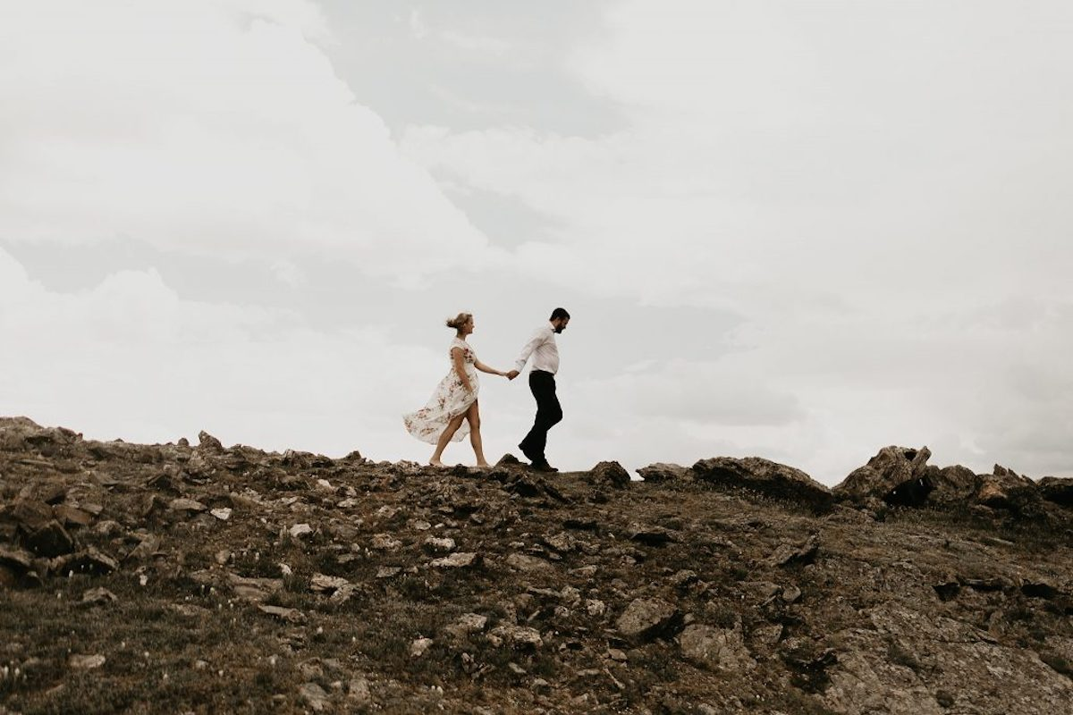 colorado_engagement_woman_holding_hands_walking_with_fiance_rocky_ground.jpg