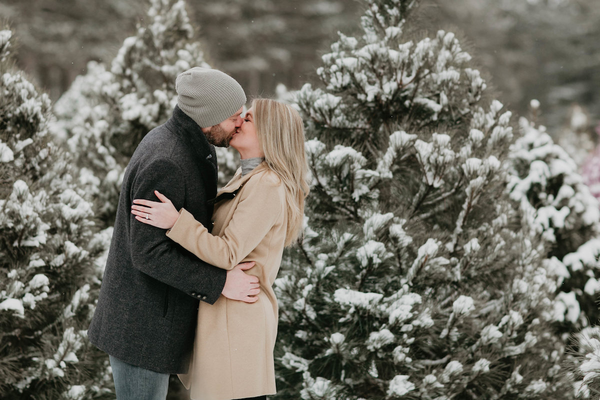 cople_kissing_in_front_of_snowy_trees.jpg