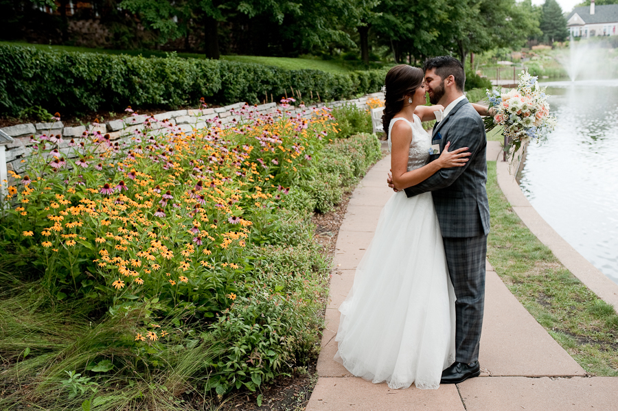 couple_almost_kissing_bride_groom_yellow_flowers_pond.jpg