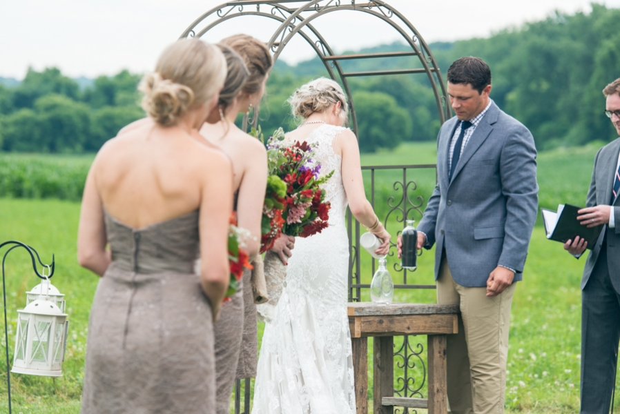 couple_at_outdoor_farm_wedding_altar_pouring_sand_in_vase.jpg