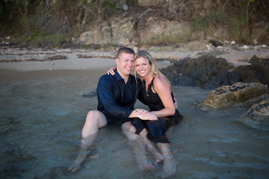 couple_engagement_photo_sitting_in_water_smiling.jpg