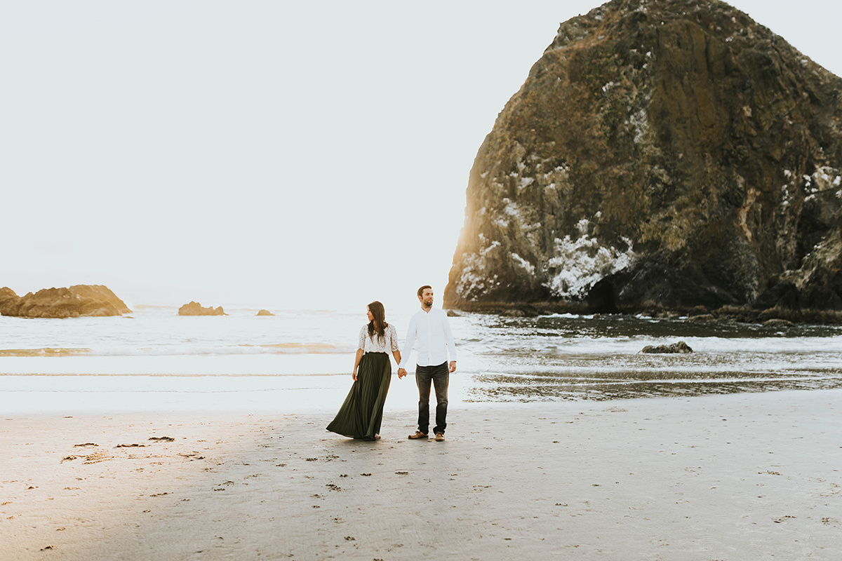couple_holding_hands_sunset_oregon_beach_looking_away.jpg