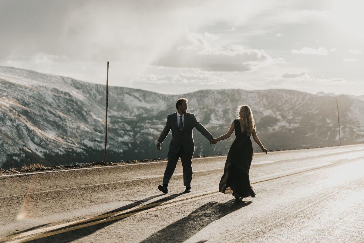 couple_holding_hands_walking_in_middle_of_street_mountains.jpg
