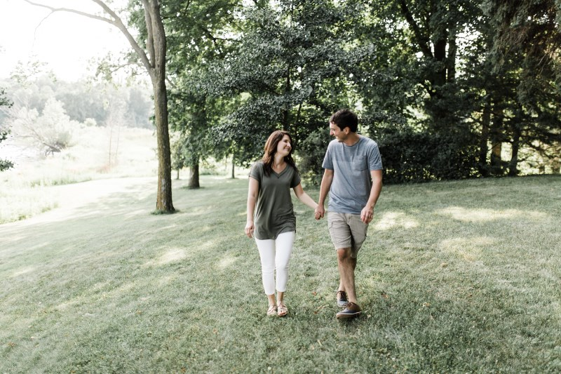 couple_holding_hands_walking_on_grass.jpg