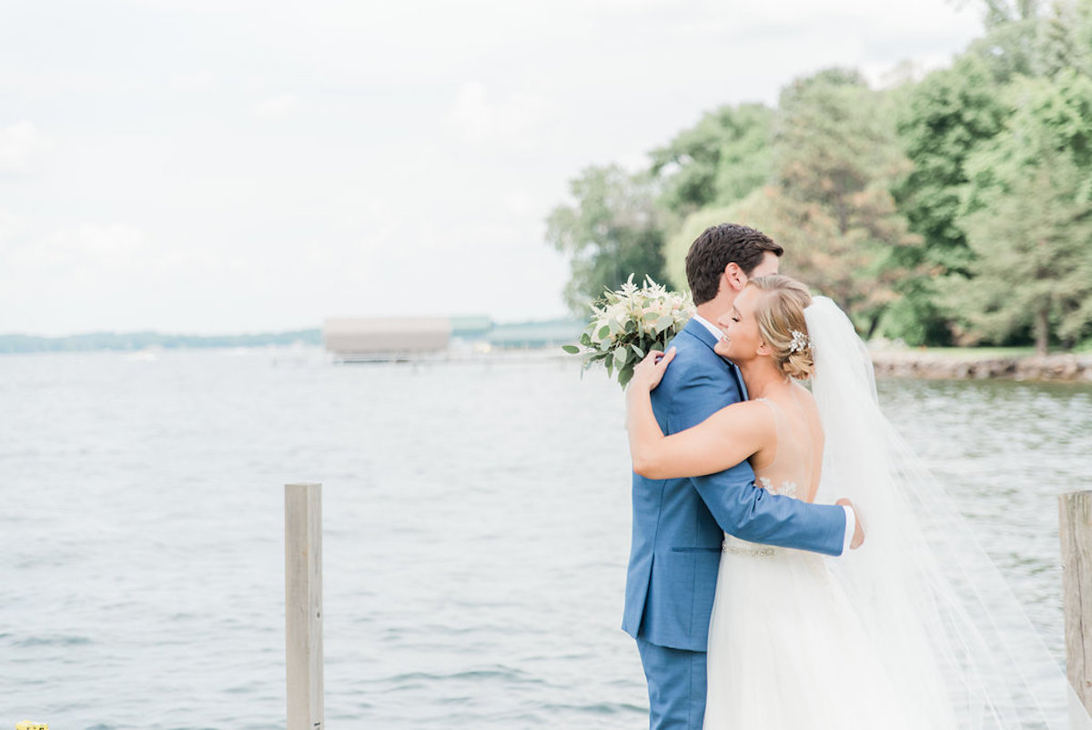 couple_hugging_on_lake_dock_navy_suit.jpg