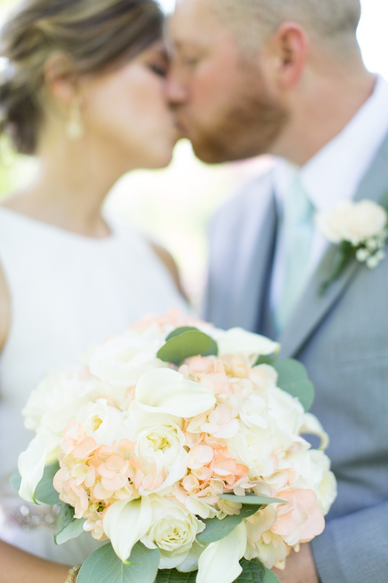 couple_kissing_blurry_in_focus_on_light_bouquet.jpg