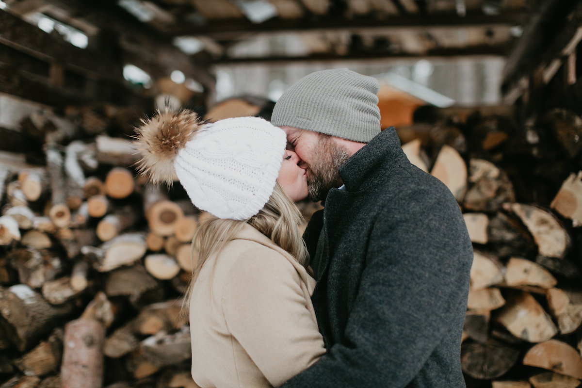 couple_kissing_in_cold_weather_wood_stack.jpg