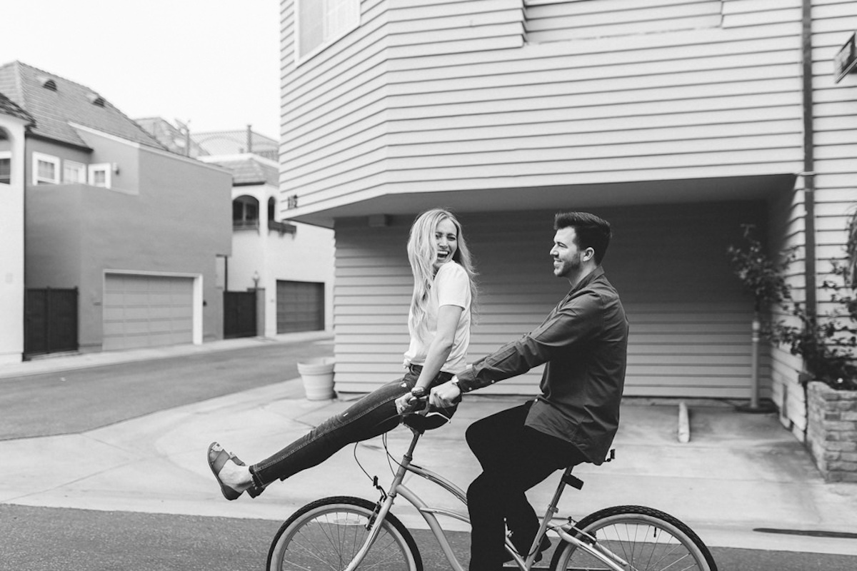couple_laughing_fiance_riding_on_handlebars_of_bike_black_and_white.JPG