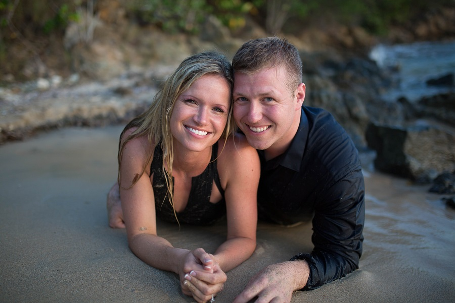 couple_laying_on_beach_engagement_photos_smiling_at_camera.jpg