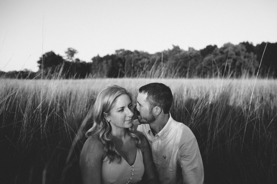 couple_sitting_in_tall_grass_field_black_and_white_photo.jpg