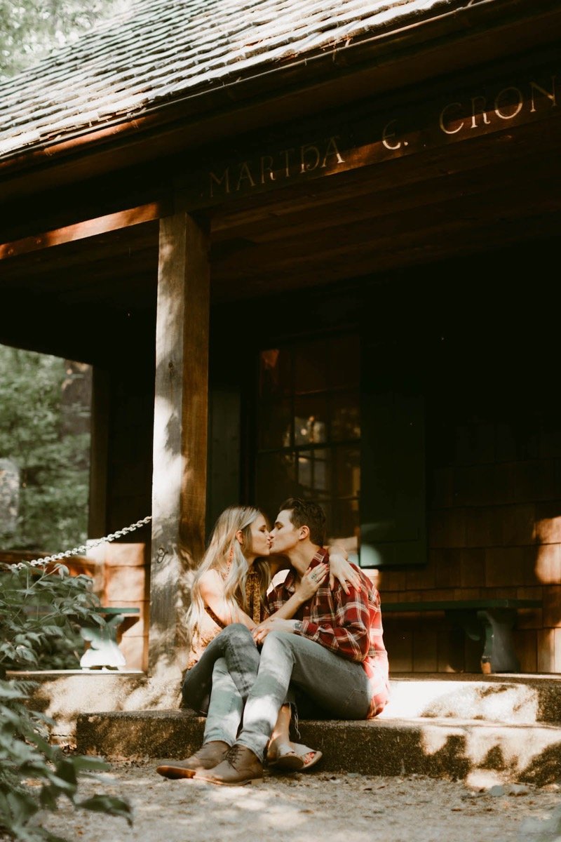 couple_sitting_on_cabins_steps_kissing_in_woods.jpg