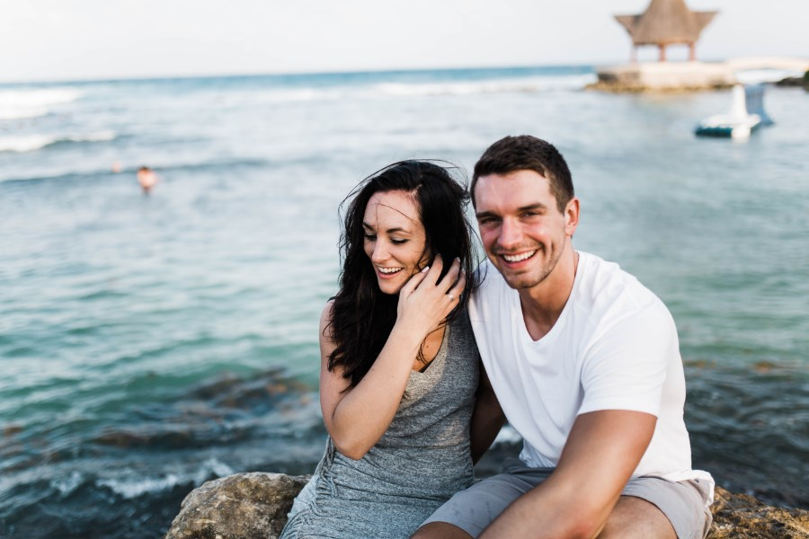 couple_sitting_on_rock_above_mexico_ocean.jpg