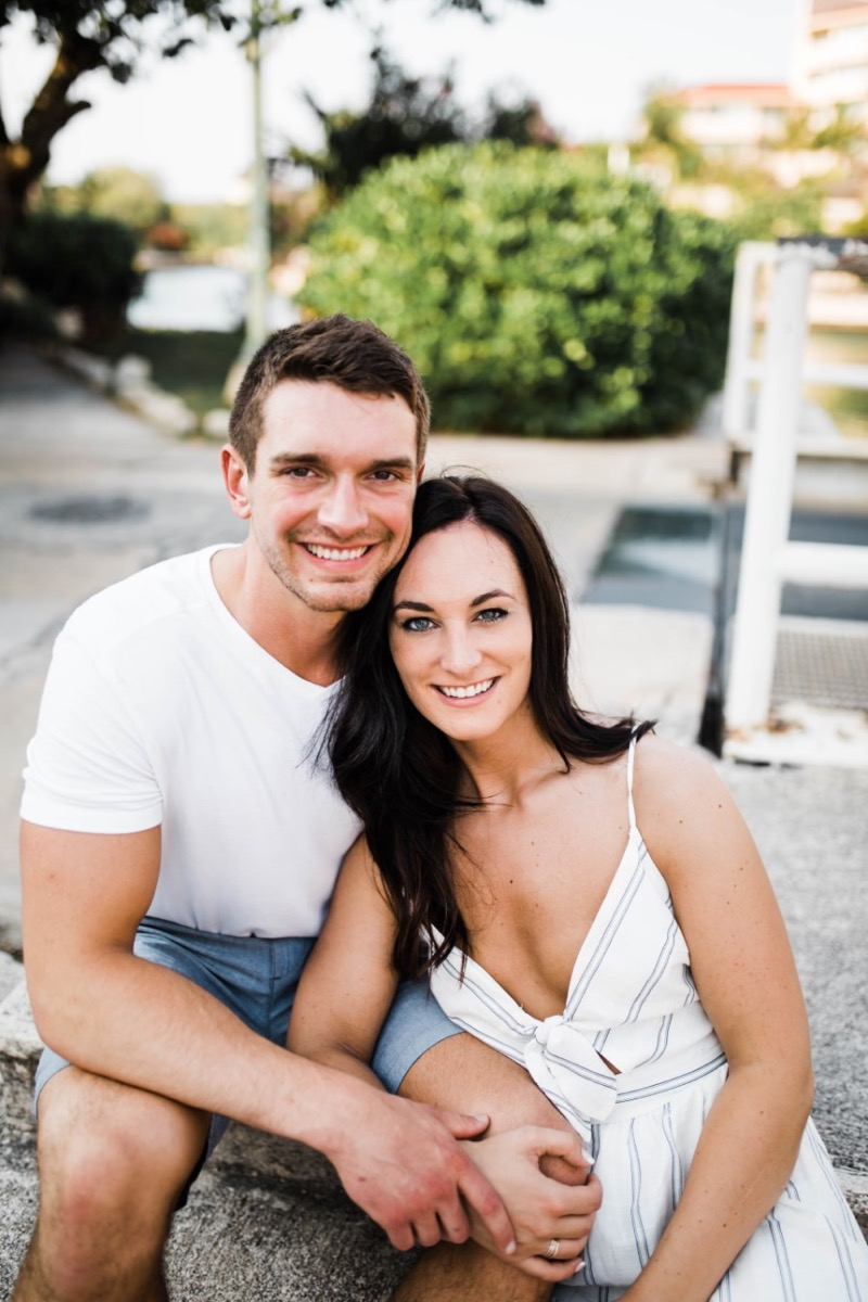 couple_sitting_smiling_at_camera_white_clothes.jpg