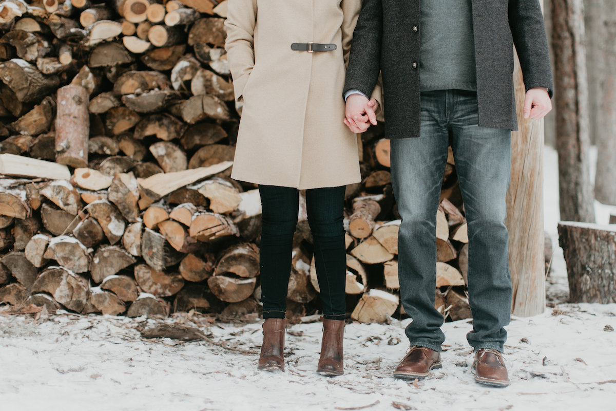 couple_standing_holding_hands_by_snowy_logs.jpg