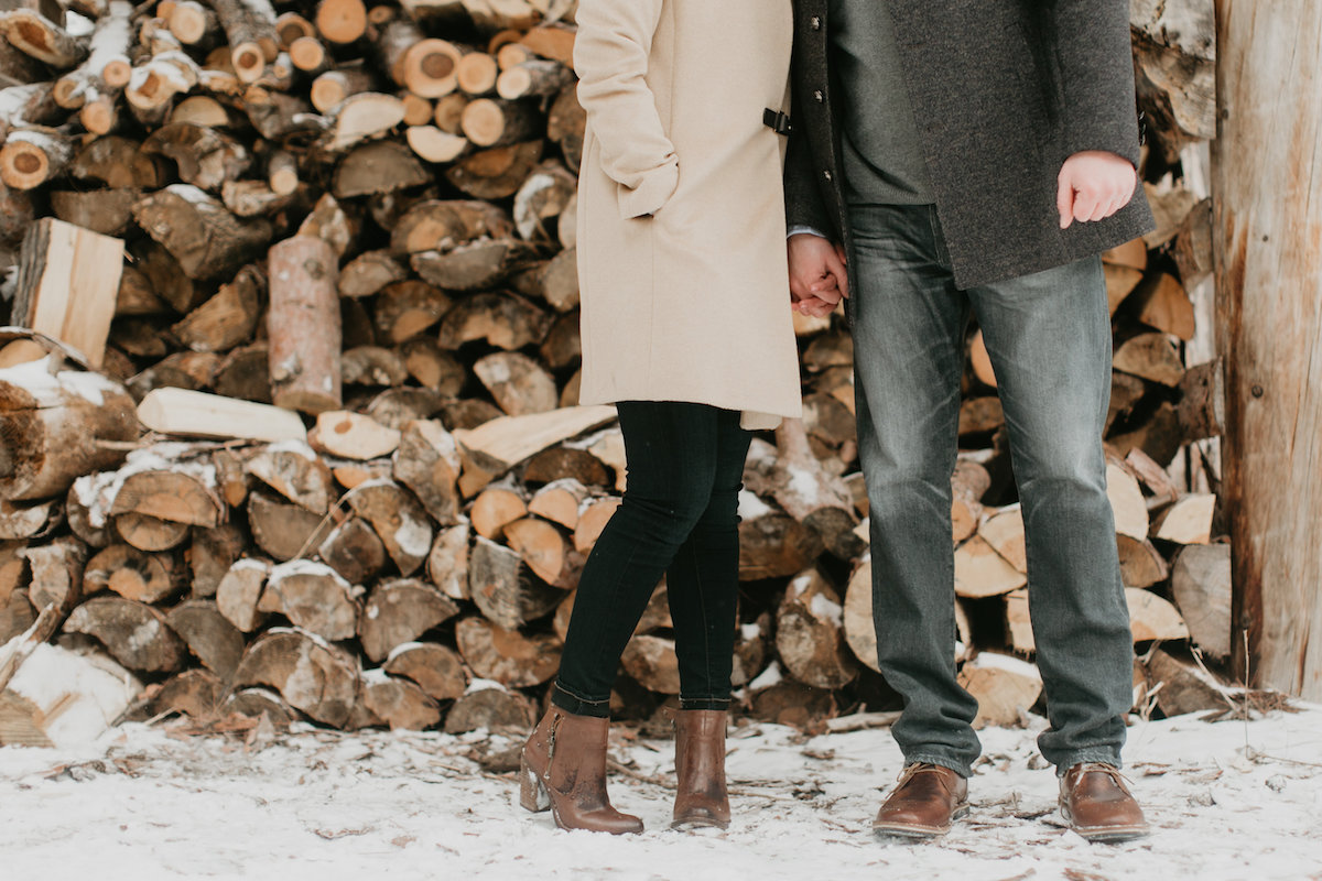 couple_standing_kissing_by_snowy_logs.jpg