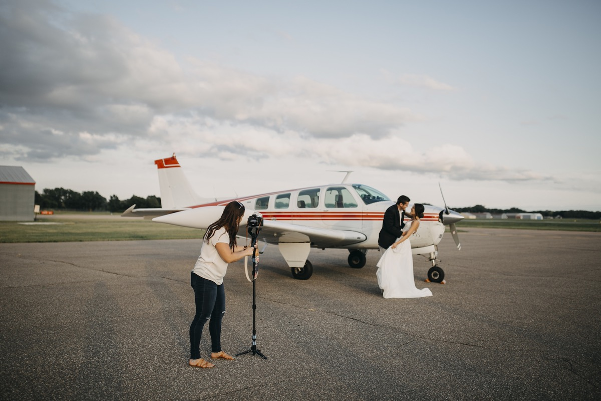 couple_wedding_standing_by_small_white_plane_red_stripes.jpg