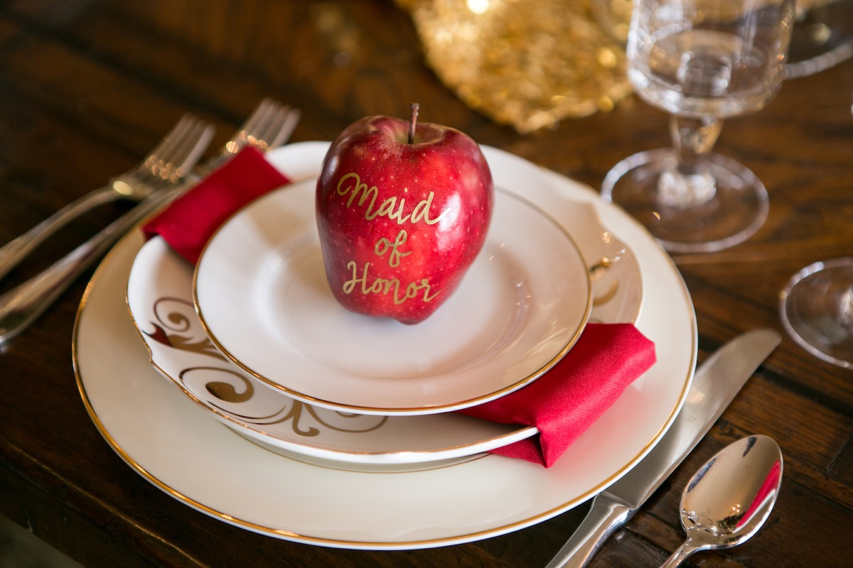 creative_wedding_reception_real_apple_placecards_with_names_handwritten_in_gold_lettering_on_white_plates.jpg