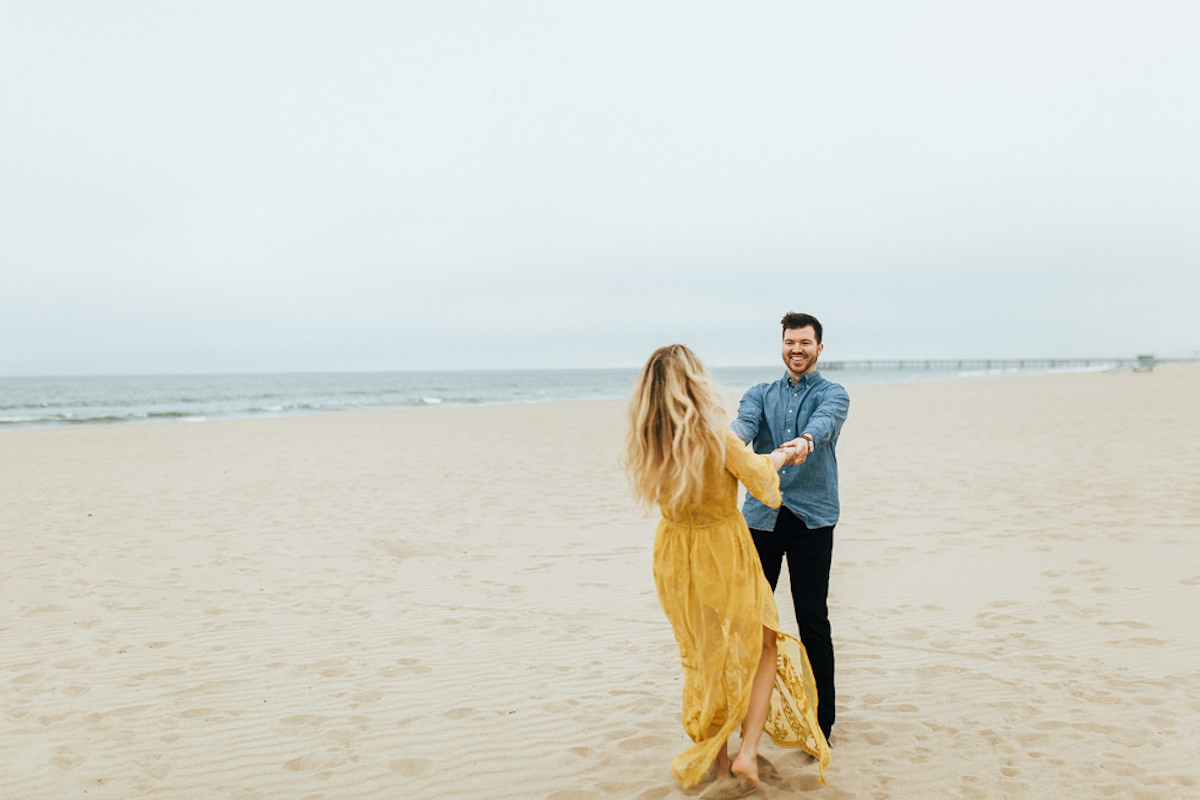 cute_couple_dancing_on_california_sand_woman_in_yellow_dress.JPG