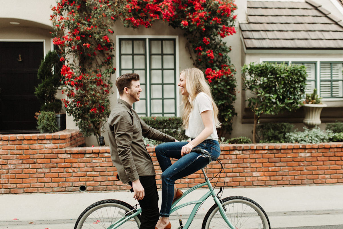 cute_couple_woman_sitting_on_bike_handlebars_laughing_with_fiance_red_flowers.JPG