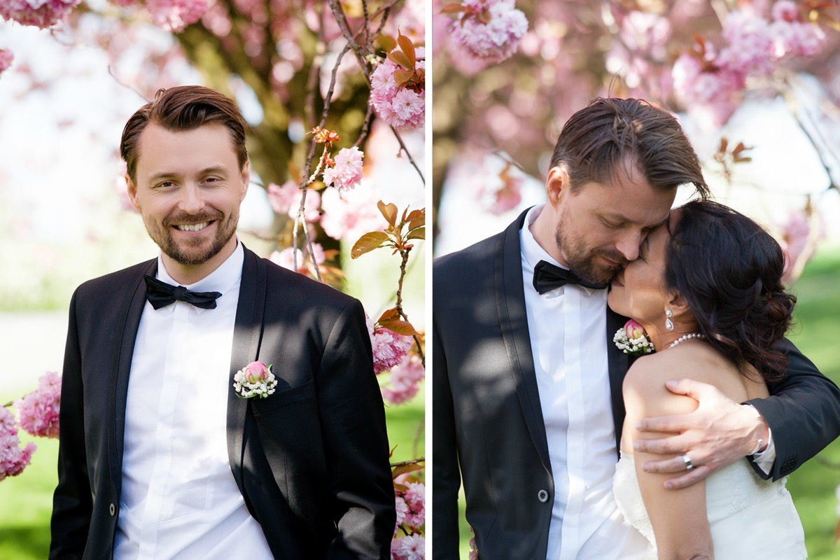 dapper_groom_hugging_bride_by_pink_cherry_trees.jpg