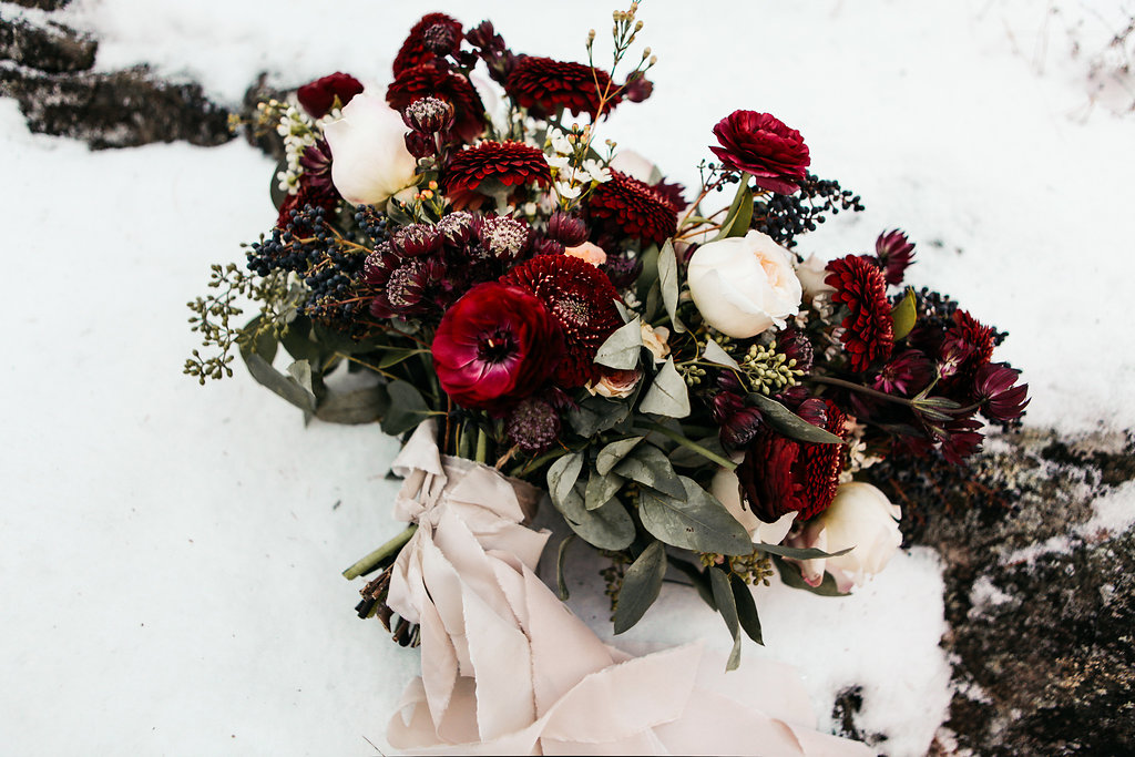 deep_red_bouquet_blush_ribbon_laying_in_snow.jpg