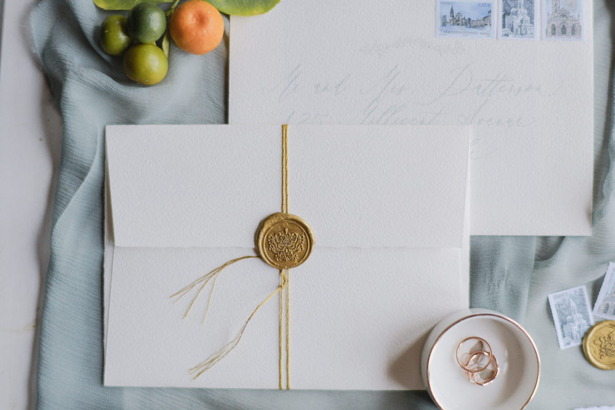 delicate_white_wedding_invitations_and_rings_against_blue_fabric.jpg