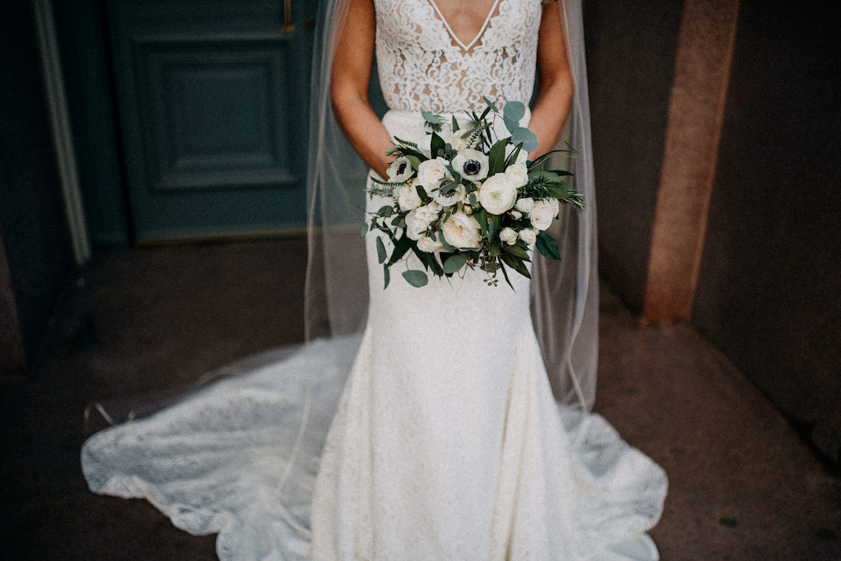 details_of_lace_bridal_gown_and_white_rose_bouquet_against_brown_building.jpg