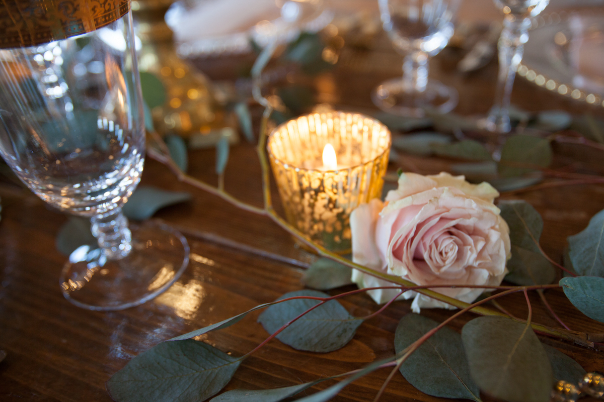 details_of_wooden_wedding_table_pink_roses_gold_candles_glasses.jpg