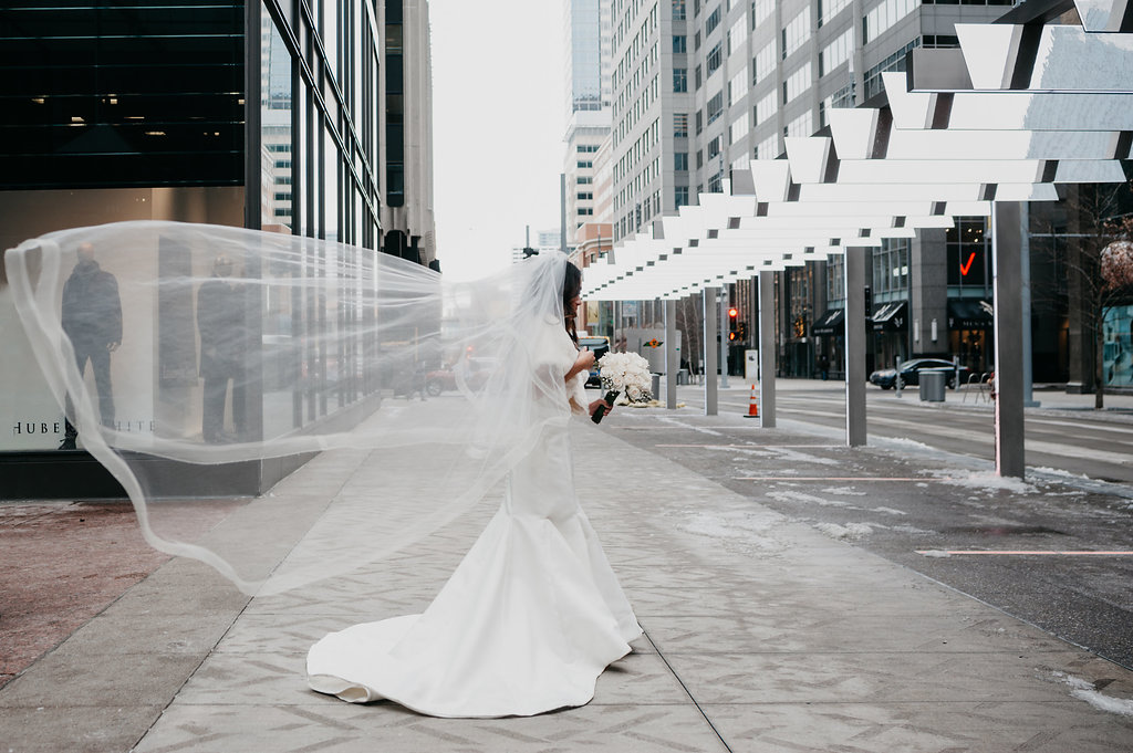 dramatic_bride_walking_in_city_veil_flowing_in_wind.jpg