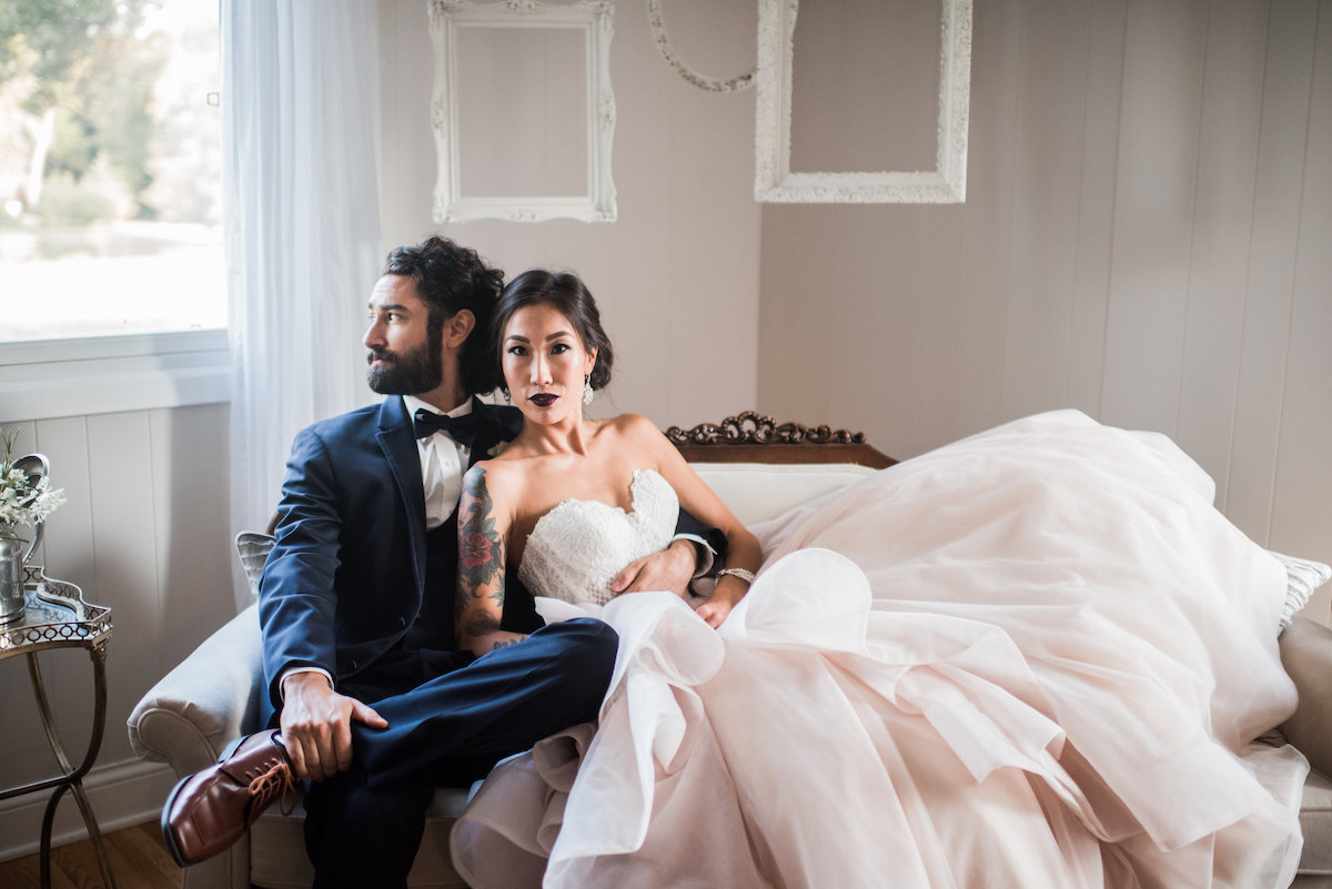 elegant_bride_and_groom_sitting_on_couch_serious.jpg