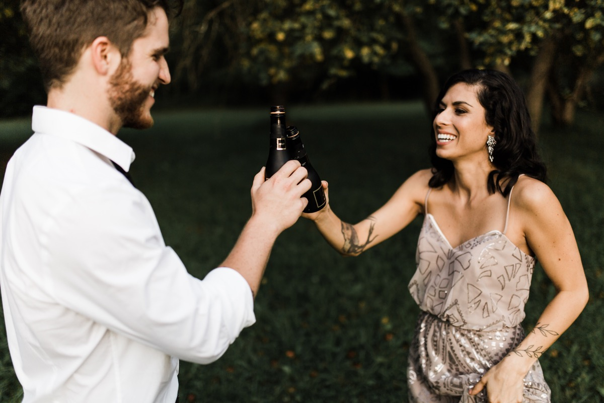engaged_couple_champagne_cheers_toast_outside.jpg