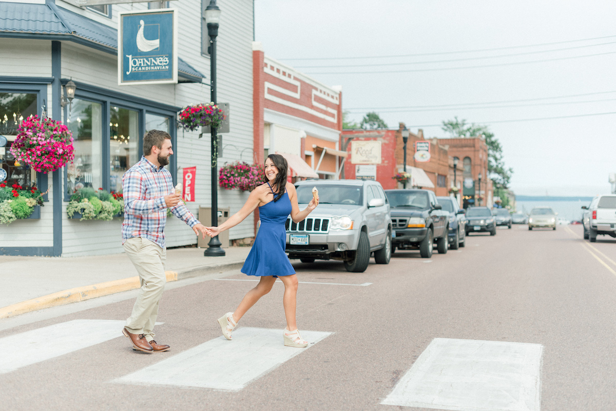 engaged_couple_crossing_street_in_cute_town_eating_ice_cream.jpg