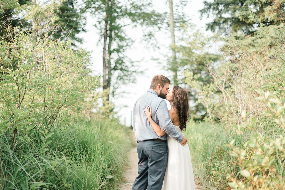 engaged_couple_embracing_between_bright_green_trees_on_sunny_path_in_woods.jpg