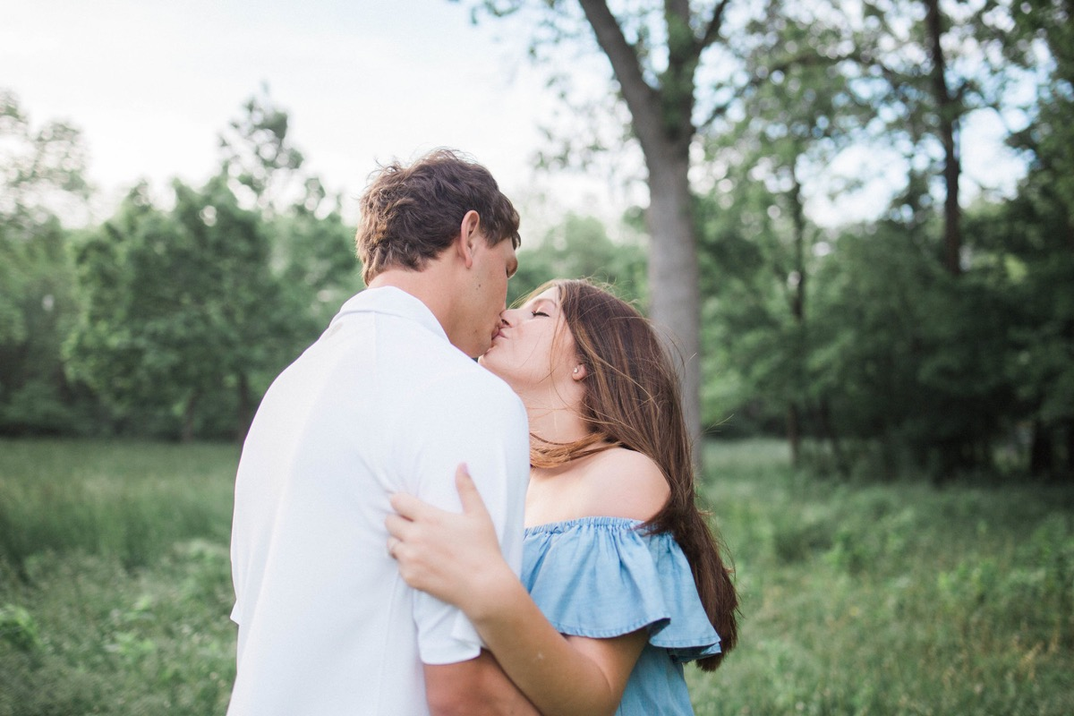 engaged_couple_kissing_in_field_white_shirt_blue_dress.jpg