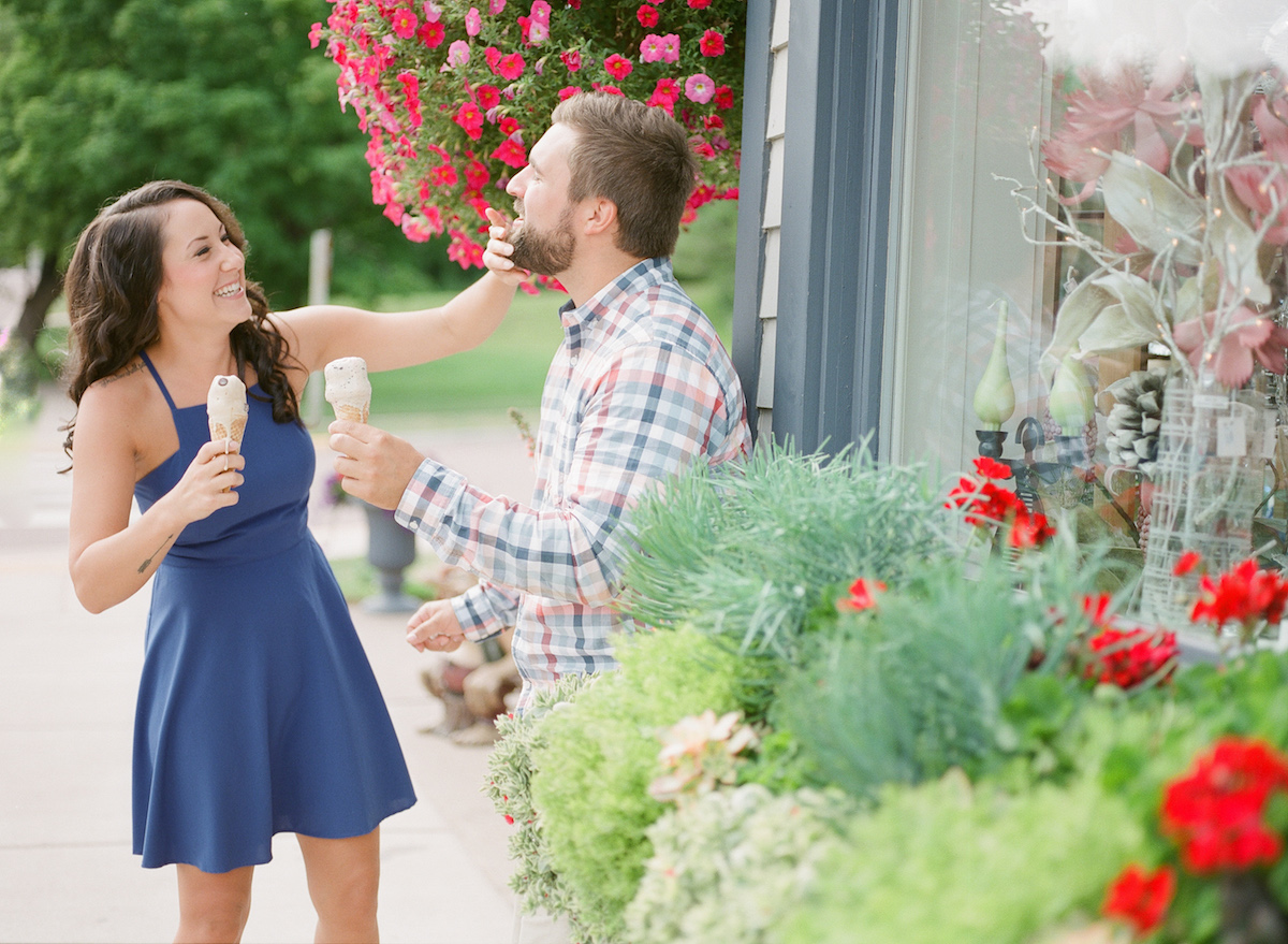engaged_couple_laughing_eating_ice_cream_by_shop_with_flowers.jpg