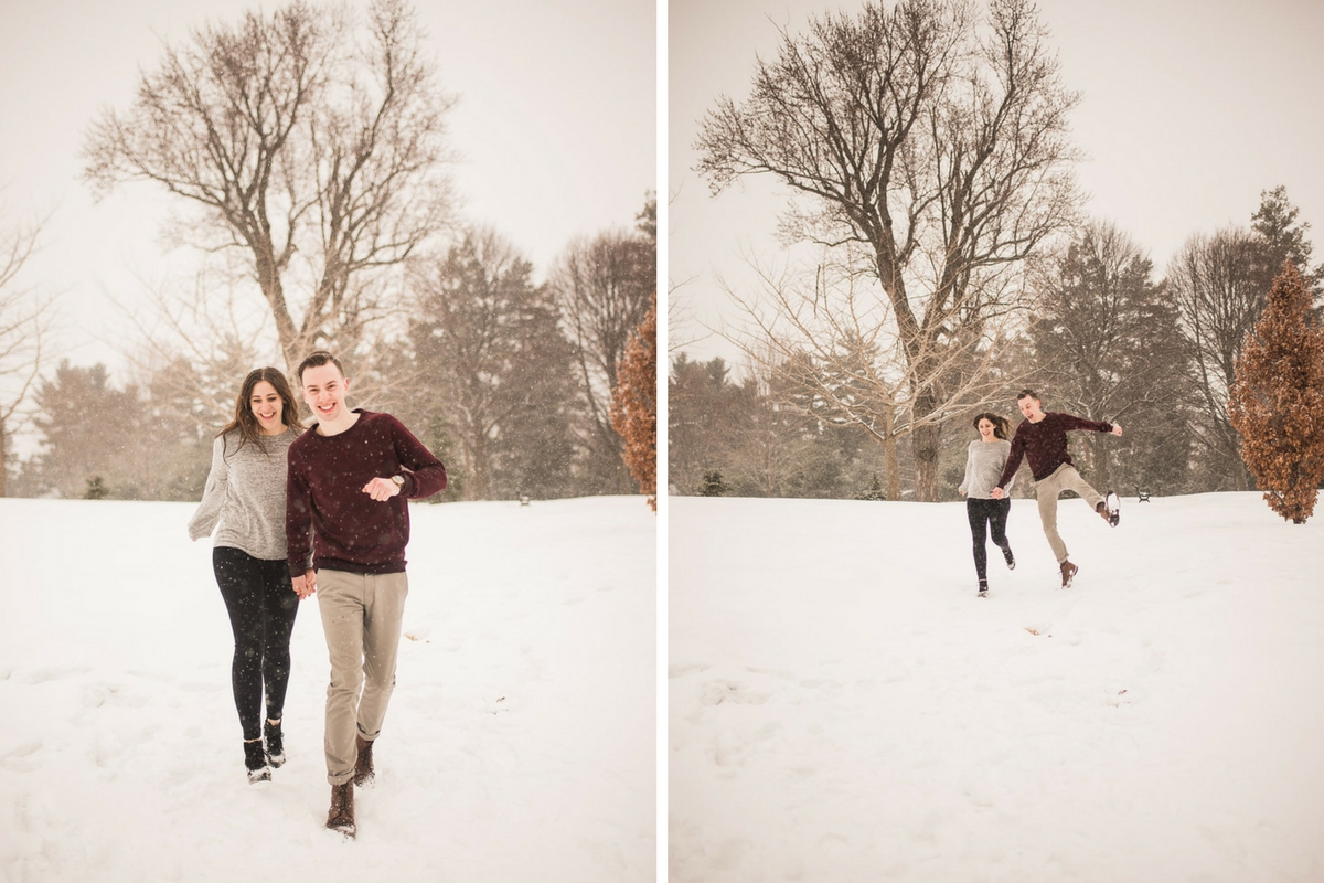 engaged_couple_running_through_snow_winter_trees_laughing.jpg