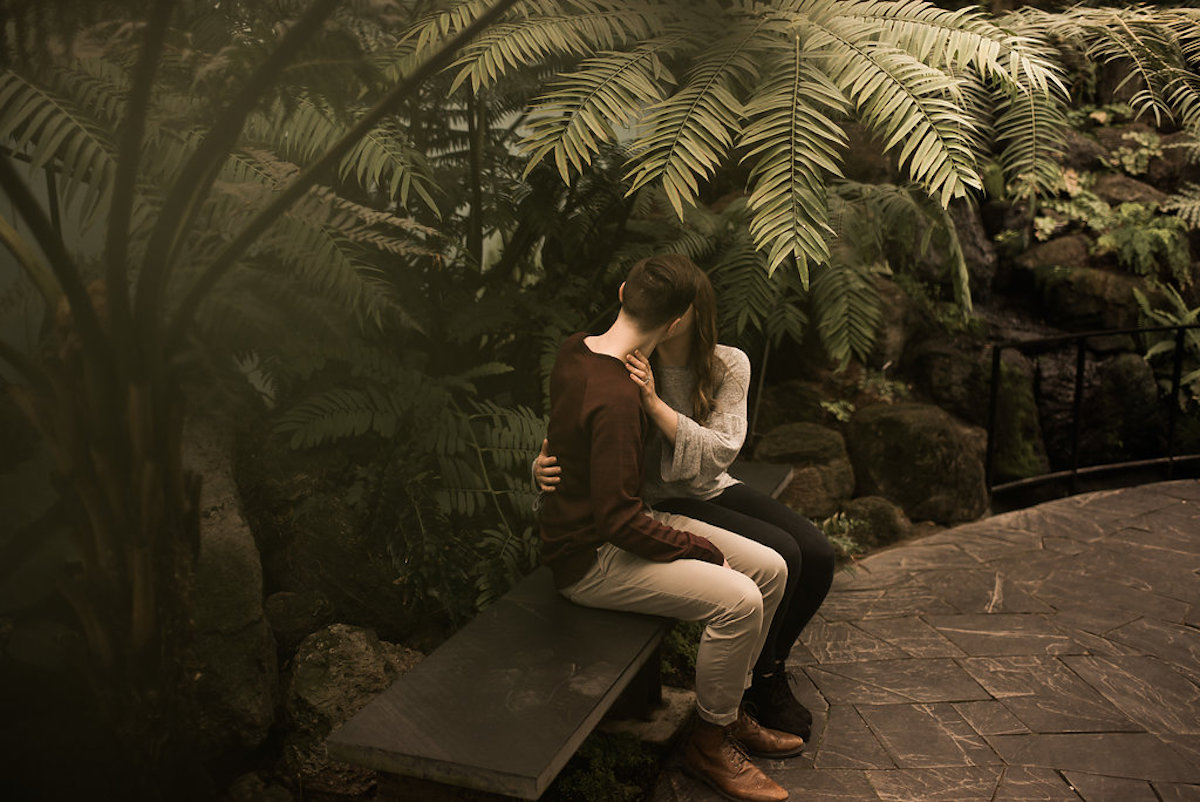 engaged_couple_sit_on_bench_indoor_garden_stones.JPG
