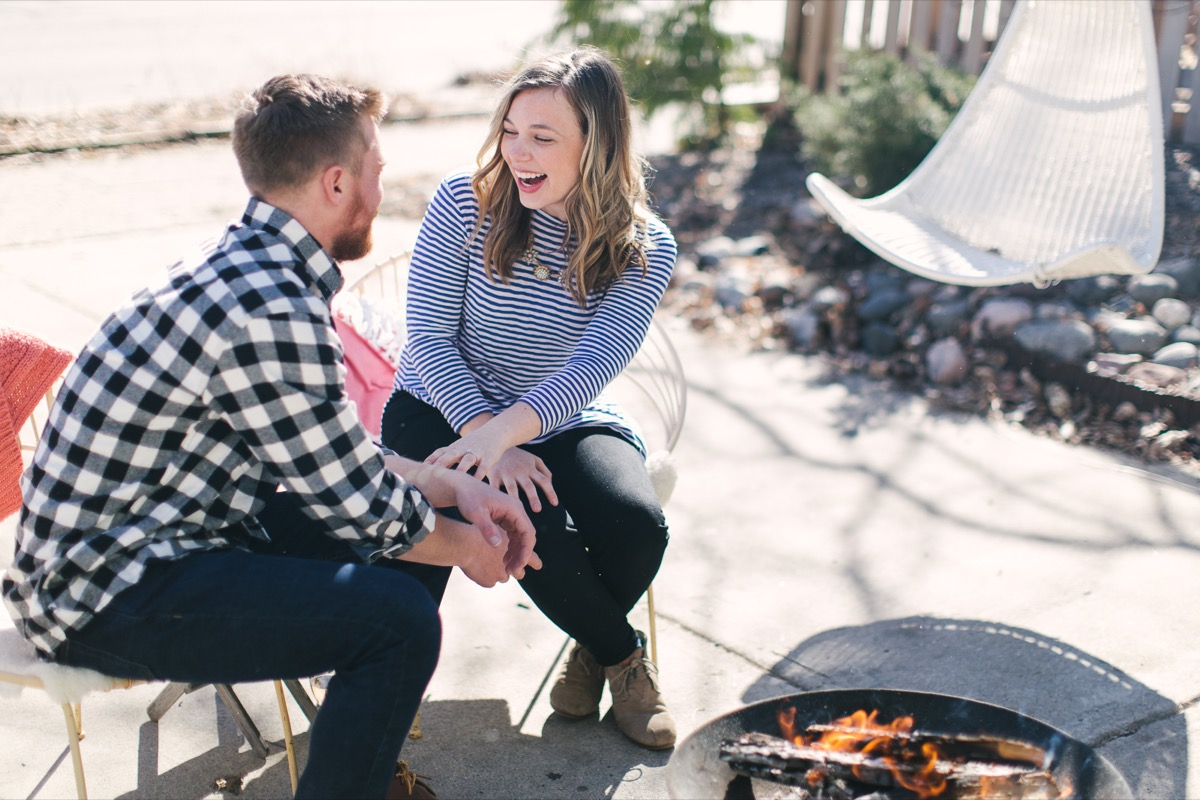 engaged_couple_sitting_outside_at_bonfire_after_creative_proposal.jpg