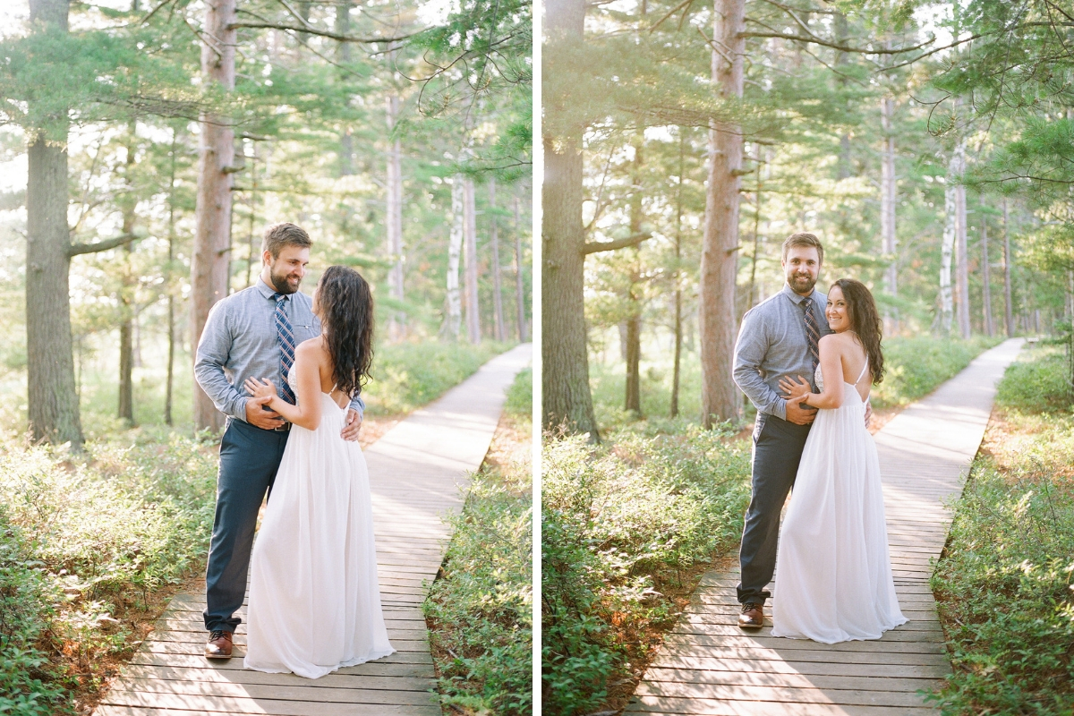 engaged_couple_smiling_happily_on_bright_sunny_trail_in_woods.jpg
