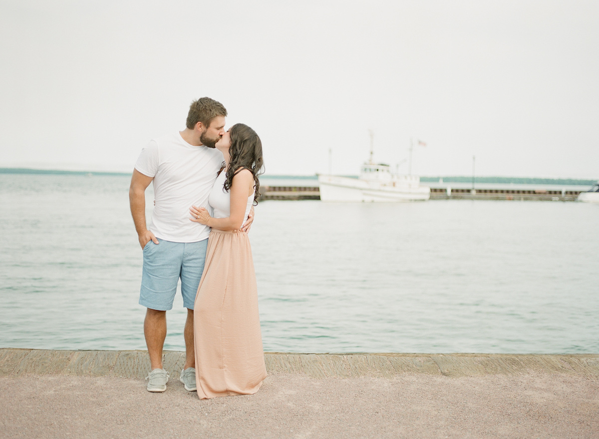 engaged_couple_standing_on_pier_sailboa_in_background.jpg