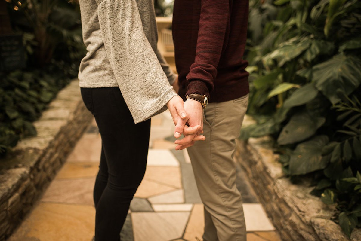 engaged_couple_standing_on_stone_path_indoor_trees.JPG