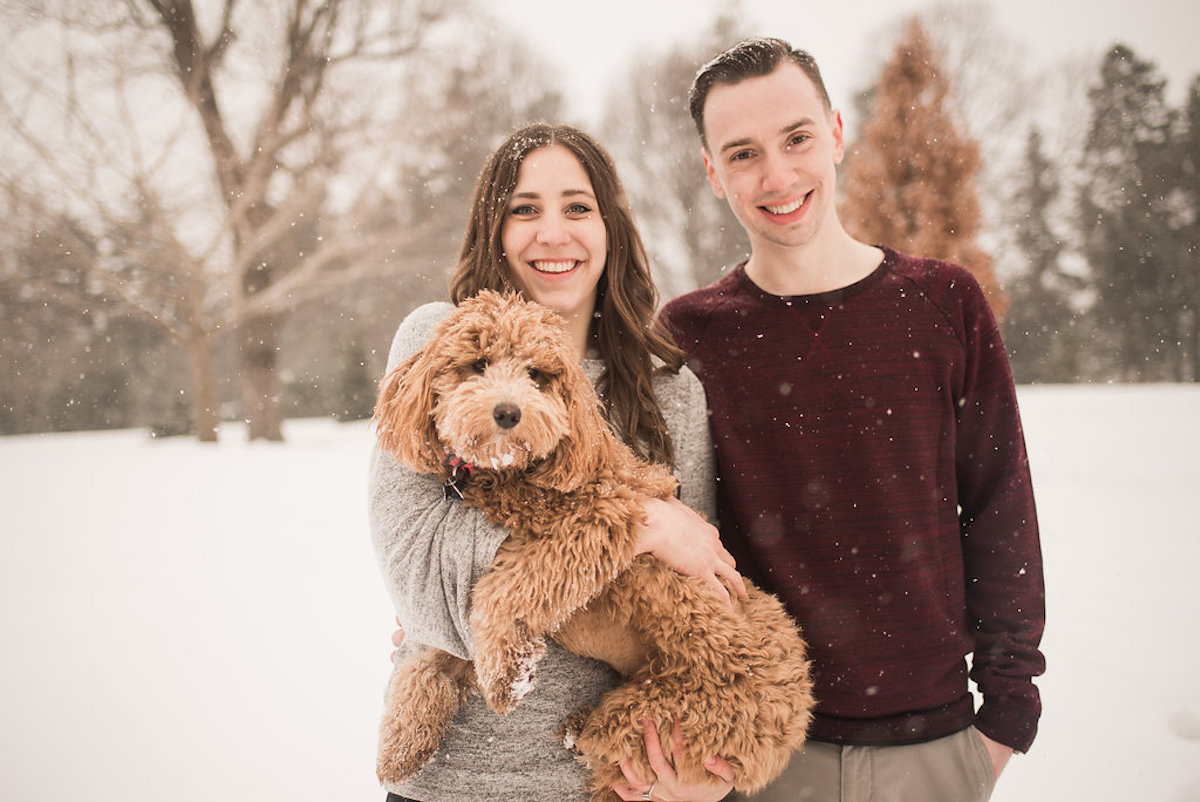 engaged_couple_standing_winter_snow_holding_goldendoodle.JPG