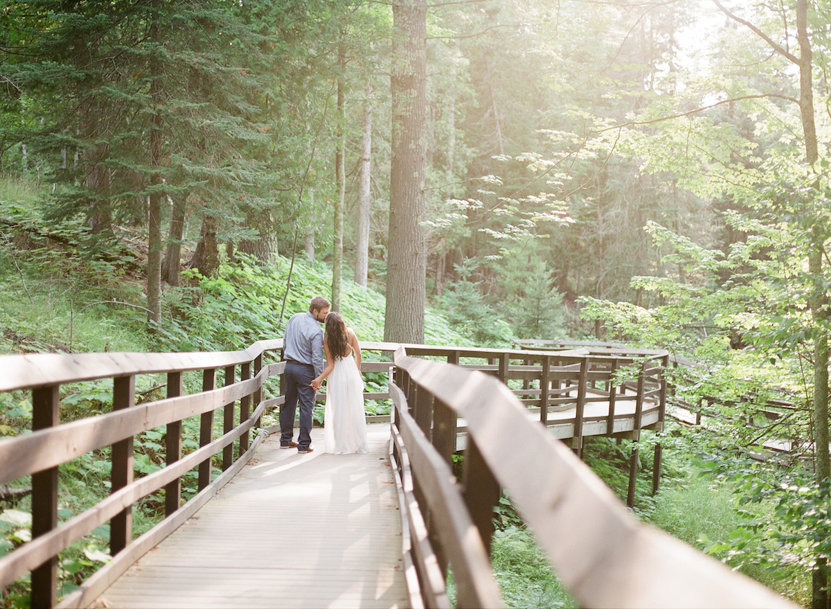 engaged_couple_walking_holding_hands_on_brown_wooden_bridge_in_bright_green_forest.jpg