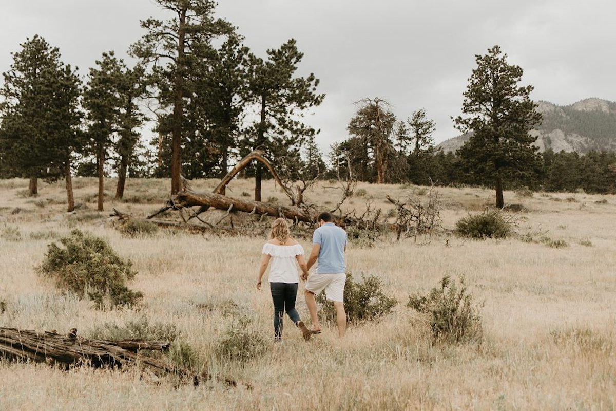 engagement_photo_couple_walking_through_Colorado_field_trees_mountains_in_background.jpg