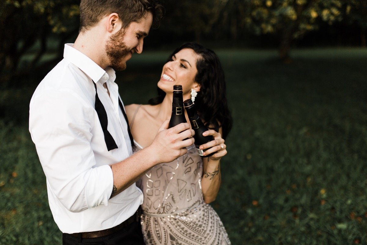 engagement_photos_cheersing_with_champagne_bottles.jpg