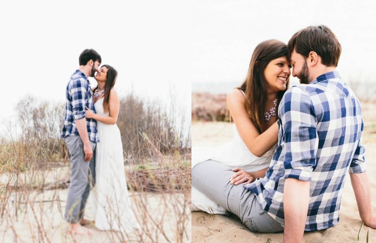 engagement_photos_couple_in_sand_at_lakeside_beach_smiling_at_each_other.jpg