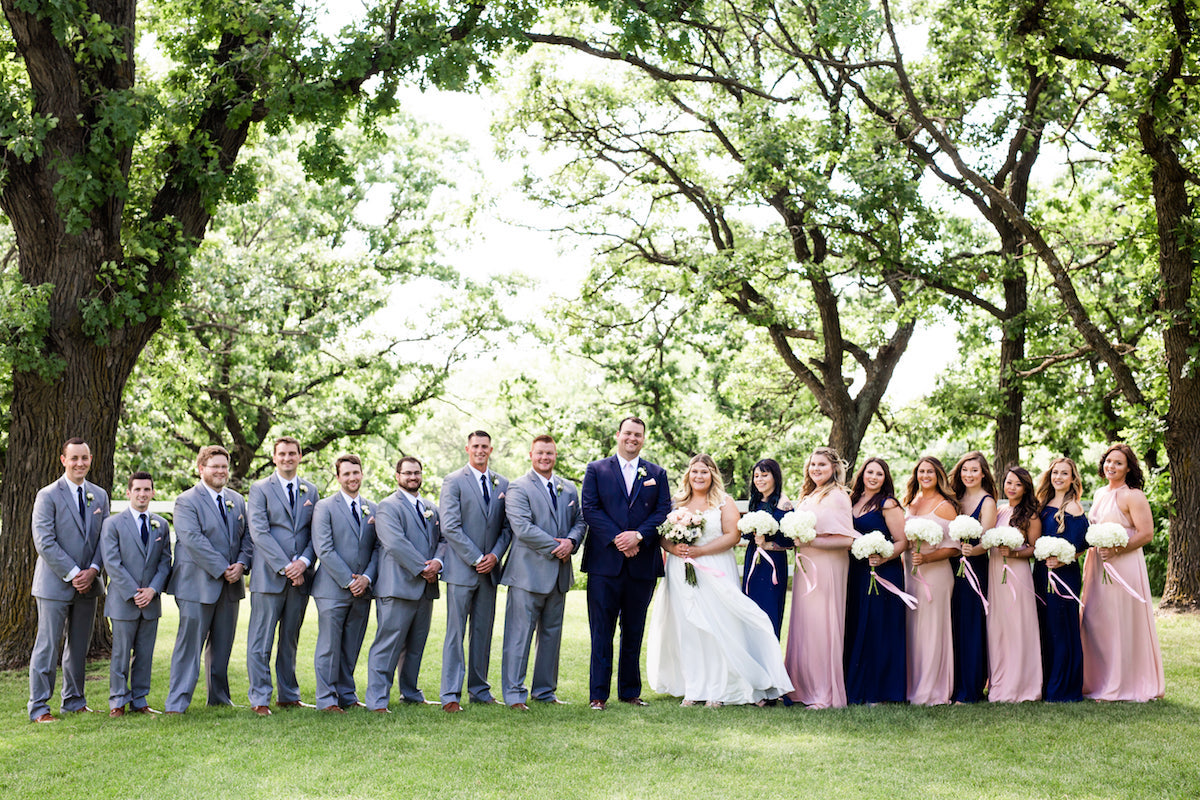 entire_bridal_party_standing_outside_sunny_farm_venue_with_large_trees_grey_groomsmen_suits_navy_pink_bridesmaid_dresses.jpg