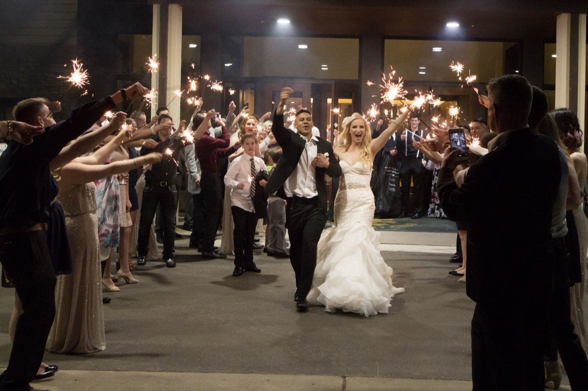 excited_newlyweds_sparkler_exit_nighttime.jpg