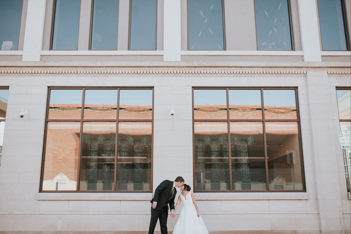 far_away_kiss_of_bride_and_groom_standing_front_of_building.jpg
