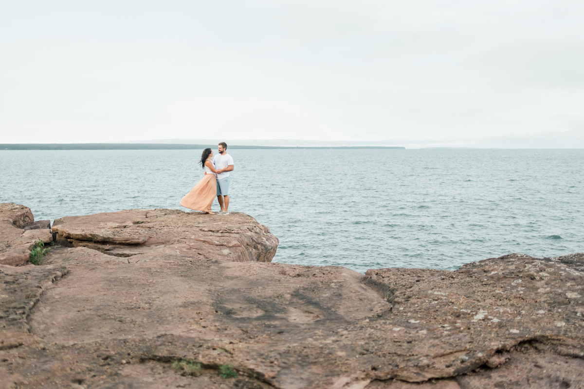 far_away_view_of_engaged_couple_standing_on_cliff_above_water_holding_each_other.jpg